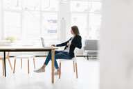 Young businesswoman sitting in office, using laptop - GUSF01677