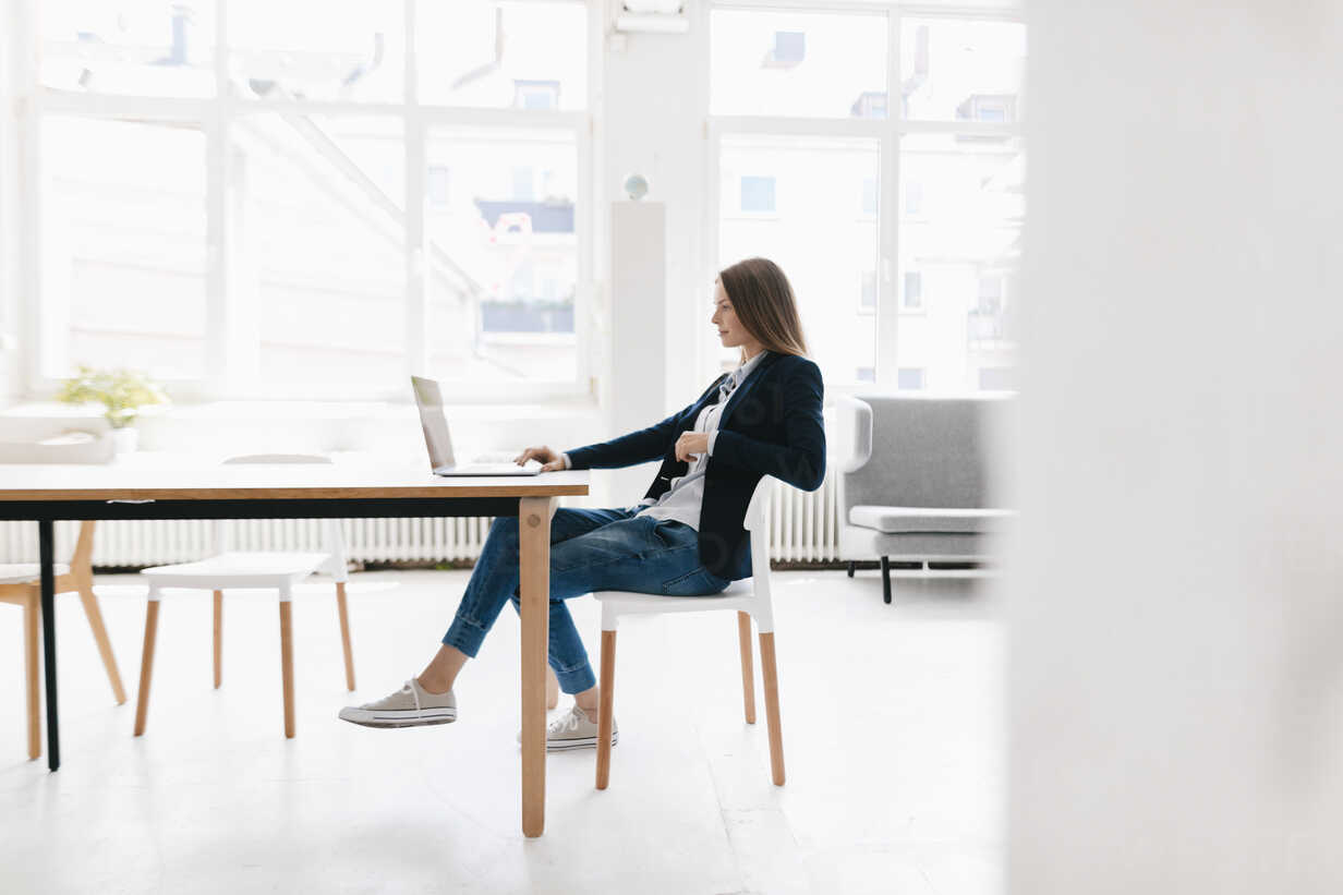 Young businesswoman sitting in office, using laptop - GUSF01677 - Gustafsson/Westend61