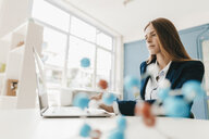 Female scientist studying molecule model - GUSF01683