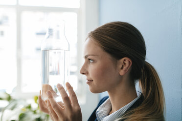 Young businesswoman holding carafe of fresh water - GUSF01689