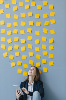 Young businesswoman usig digital tabet, sitting under data cloud - GUSF01713