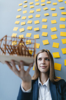 Young businesswoman holding architectural model with yellow sticky notes on the wall behind ger - GUSF01716