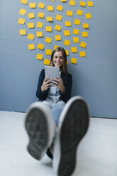 Young businesswoman sitting under data cloud, using digital tablet - GUSF01719