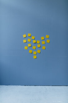 Heart-shape on a blue wall, made of yellow sticky notes - GUSF01722
