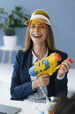 Laughing, young businesswoman, holding water gun - GUSF01737