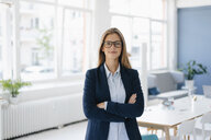 Portrait of a confident young businesswoman, standing in office - GUSF01743