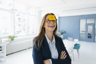 Young businesswman with yellow sticky note on her forehead, saying 'burnout' - GUSF01746