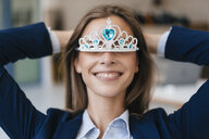 Ambitious young woman wearing crown as an award for her achievments - GUSF01755