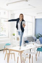 Young businesswoman balancing on one leg on desk in the board room, holding digital tablet - GUSF01761