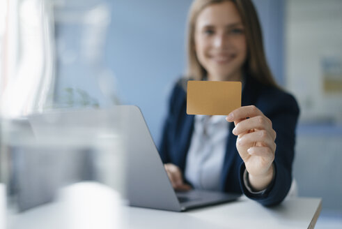 Young businesswoman doing online payment, showing her credit card - GUSF01770