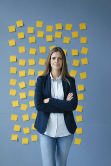 Yong businesswoman standing in front of wall, full of yellow sticky notes, with arms crossed - GUSF01776
