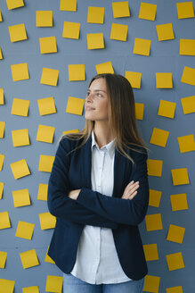 Yong businesswoman standing in front of wall, full of yellow sticky notes, with arms crossed - GUSF01779