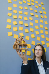 Young businesswoman holding architectural model with yellow sticky notes on the wall behind ger - GUSF01782
