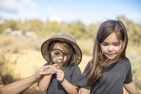 Girls examining plant with magnifying glass - ZEF16073