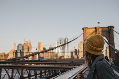 USA, New York, New York City, female tourist on Brooklyn Bridge in the morning light - LHPF00317