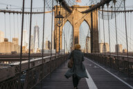 USA, New York, New York City, female tourist on Brooklyn Bridge in the morning light - LHPF00320