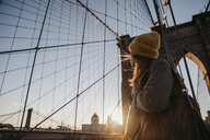 USA, New York, New York City, female tourist on Brooklyn Bridge at sunrise - LHPF00323
