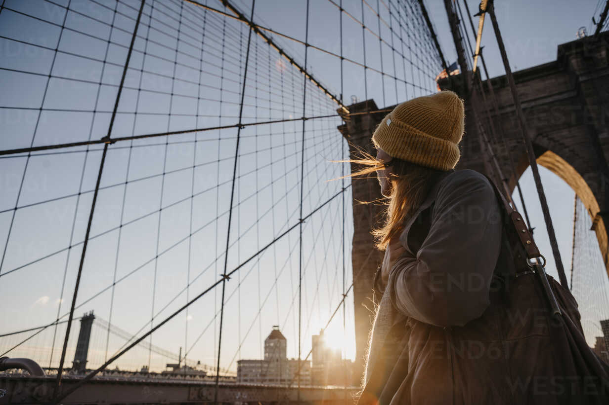 USA, New York, New York City, female tourist on Brooklyn Bridge at sunrise - LHPF00323 - letizia haessig photography/Westend61