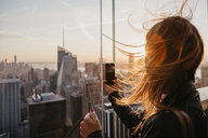 USA, New York, New York City, woman taking a photo at sunrise - LHPF00332