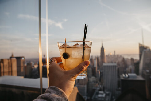 USA, New York, New York City, hand with cocktail glass at sunrise - LHPF00335