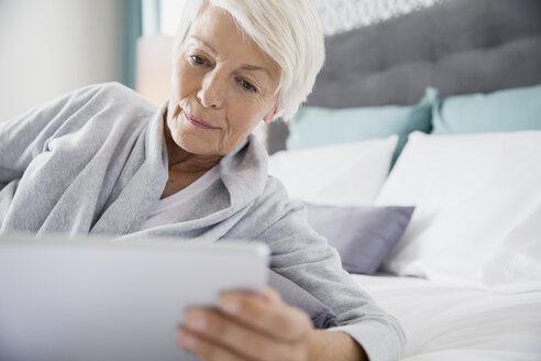 Woman using digital tablet in bed - HEROF03051