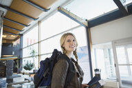Smiling woman with backpack in airport - HEROF03063