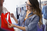 Woman checking price on tank-top in shop - HEROF03114
