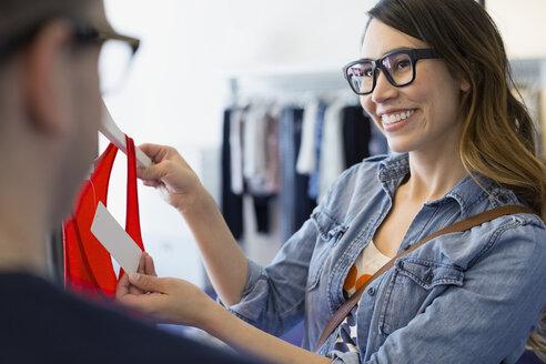 Woman checking price on tank-top in shop - HEROF03117