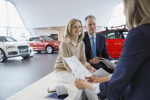 Saleswoman and couple finalizing paperwork in car dealership - HEROF03177