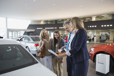 Saleswoman and family with car brochure in showroom - HEROF03198