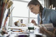 Woman painting at desk - HEROF03219