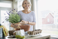Smiling woman with garden supplies - HEROF03234