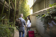 Couple with suitcases arriving at house - HEROF03297