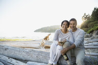 Portrait of couple drinking white wine on beach - HEROF03324