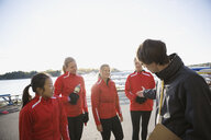 Coach talking to rowing team at waterfront - HEROF03342