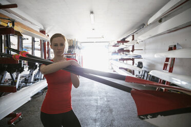Portrait of confident rower holding oars in boathouse - HEROF03345