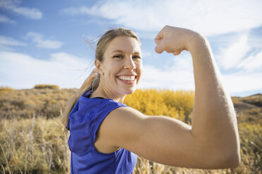 Enthusiastic woman flexing muscles in sunny rural field - HEROF03351