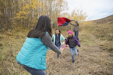 Daughters running toward mother in field - HEROF03357