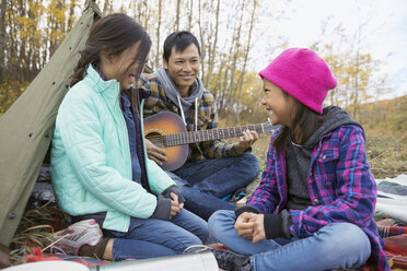 Father and daughters playing guitar at campsite - HEROF03360