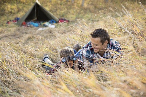 Father and son using binoculars outside tent - HEROF03363