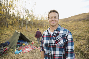Portrait of smiling man outside tent at campsite - HEROF03369