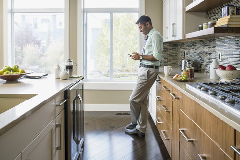 Man text messaging on cell phone in kitchen - HEROF03393