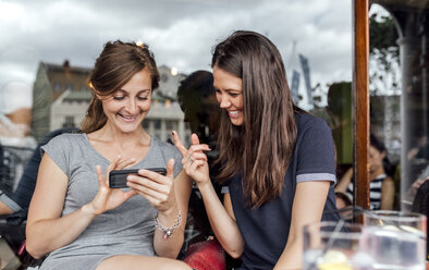 Two women having fun with their smartphone on a terrace - MGOF03883