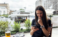Young beautiful woman using her smartphone on a terrace - MGOF03886