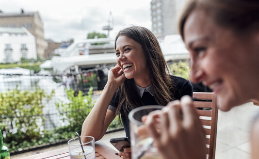 Two happy women with smartphone and drinks on a terrace - MGOF03889
