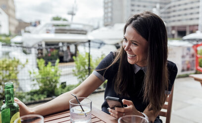 Happy young woman with smartphone and drink on a terrace - MGOF03892