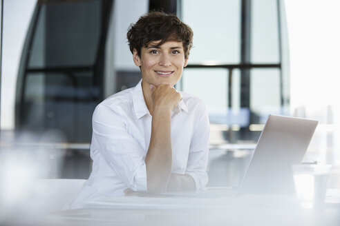 Portrait of confident businesswoman sitting at desk in office with laptop - RBF06854