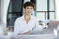 Portrait of confident businesswoman sitting at desk in office with laptop and document - RBF06857