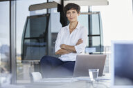 Portrait of confident businesswoman sitting on desk in office with laptop - RBF06860