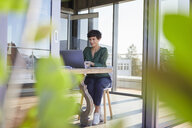 Smiling businesswoman sitting at table using laptop - RBF06863